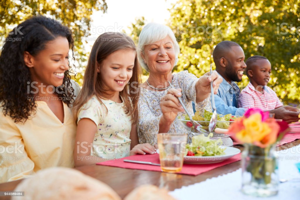 Family and friends having lunch at a table in the garden royalty-free stock photo