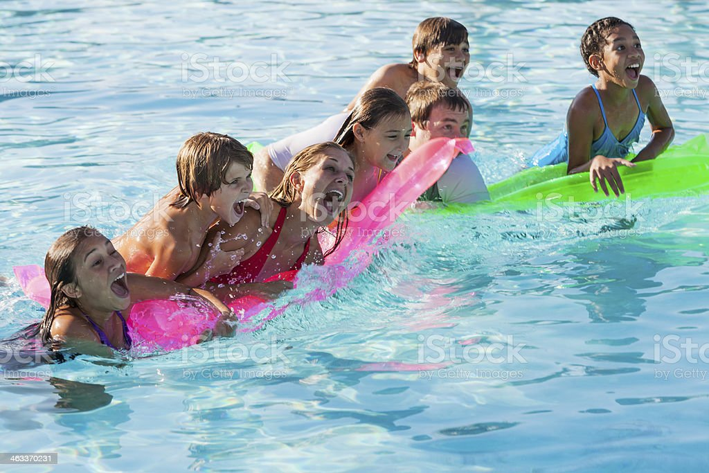 Family and friends in swimming pool stock photo