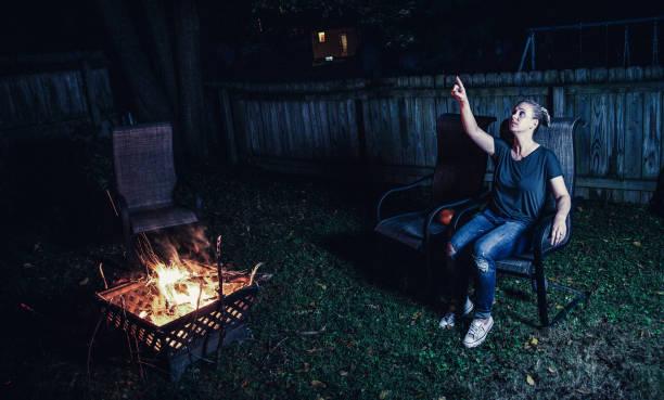 Familie und Freunde sitzen um einen Hinterhof Feuerstelle und Toast Smores – Foto