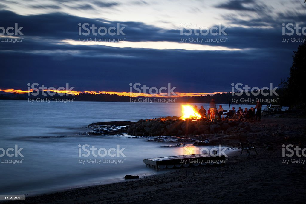Family and Friends Sitting Around Campfire at Sunset royalty-free stock photo