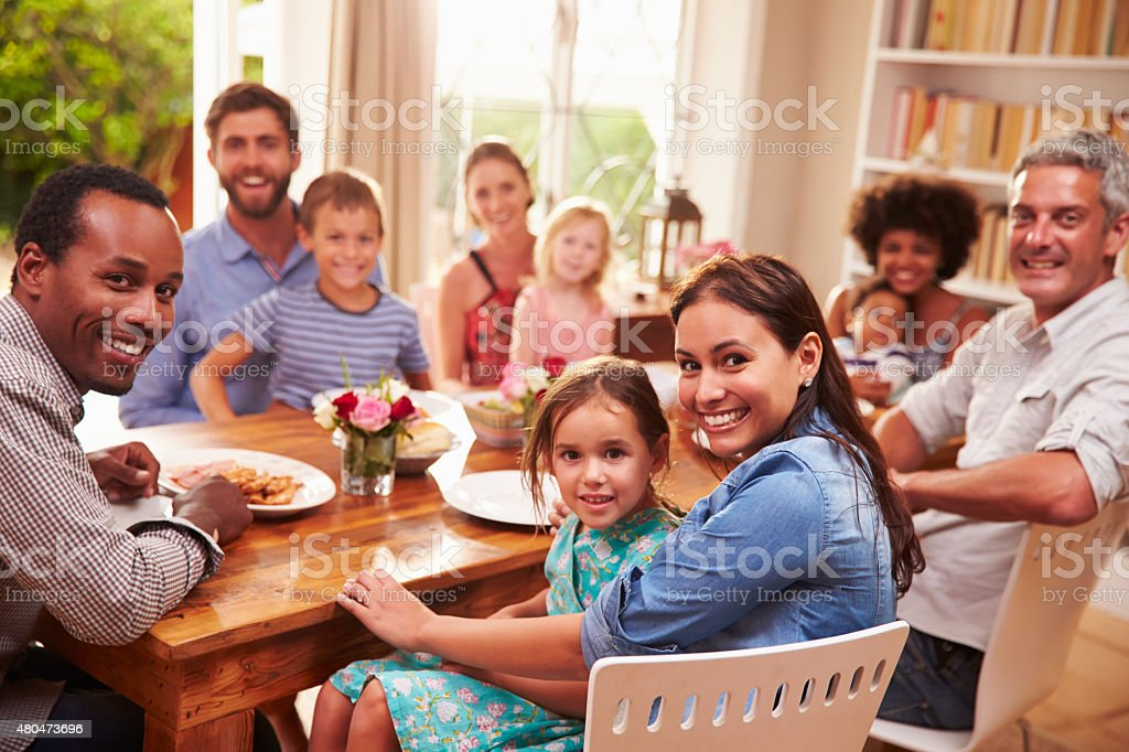 Family and friends sitting at  dining table, looking at camera stock photo