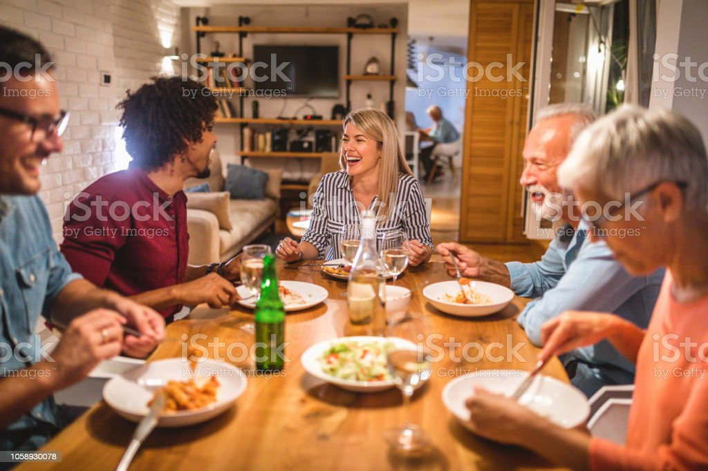 Lovely family with guests having a dinner together.