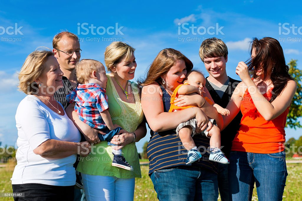 Family and multi-generation - fun on meadow in summer stock photo