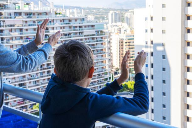 Familie applaudiert medizinischem Personal vom Balkon. Menschen klatschen während der Coronavirus-Pandemie händegewaltiger Hände auf Balkonen und Fenstern zur Unterstützung von Gesundheitspersonal – Foto