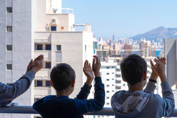 Familie applaudiert medizinischem Personal von ihrem Balkon. Menschen in Spanien klatschen Dankbarkeit auf Balkonen und Fenstern zur Unterstützung von Gesundheitspersonal, Ärzten und Krankenschwestern während der Coronavirus-Pandemie – Foto