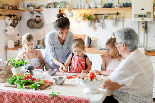 Family are cooking italian pizza in cozy home kitchen for dinner. Cute kids and grandmother are preparing homemade food. Old senior woman is teaching three girls. Children chef concept. stock photo