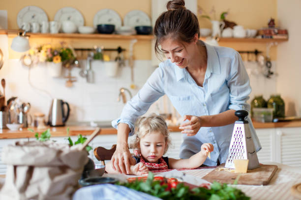 Family are cooking italian pizza in cozy home kitchen. Happy mother is teaching cute kid to prepare food or meal for Thanksgiving dinner. Little girl is helping woman. Children chef concept. stock photo