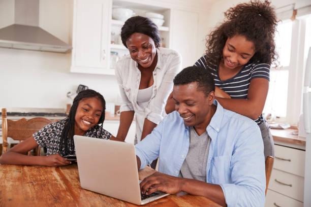 familie küchentisch zusammen buchen urlaub auf laptop - kinderküche zubehör stock-fotos und bilder