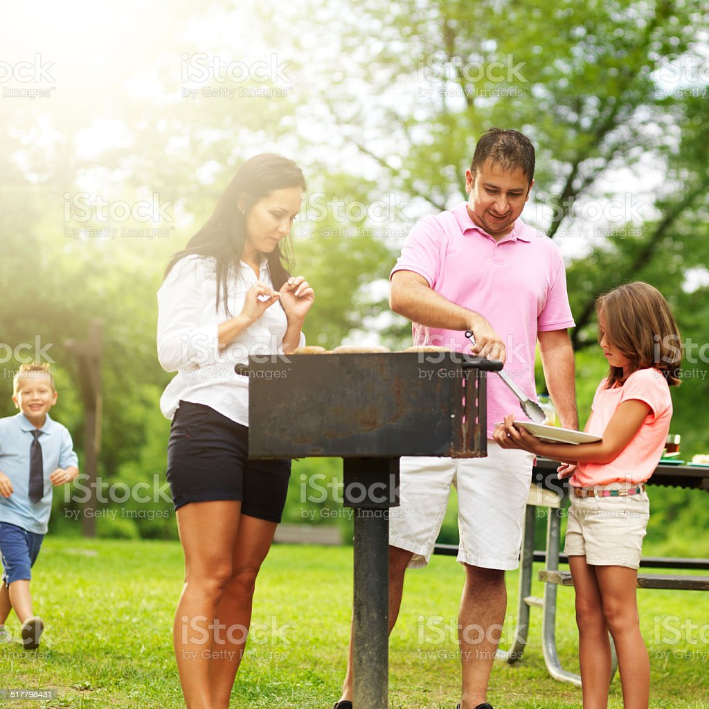 family at barbecue serving food stock photo