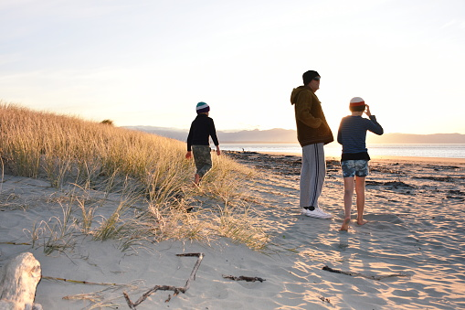 Family at Beach on Winter Evening Sunset