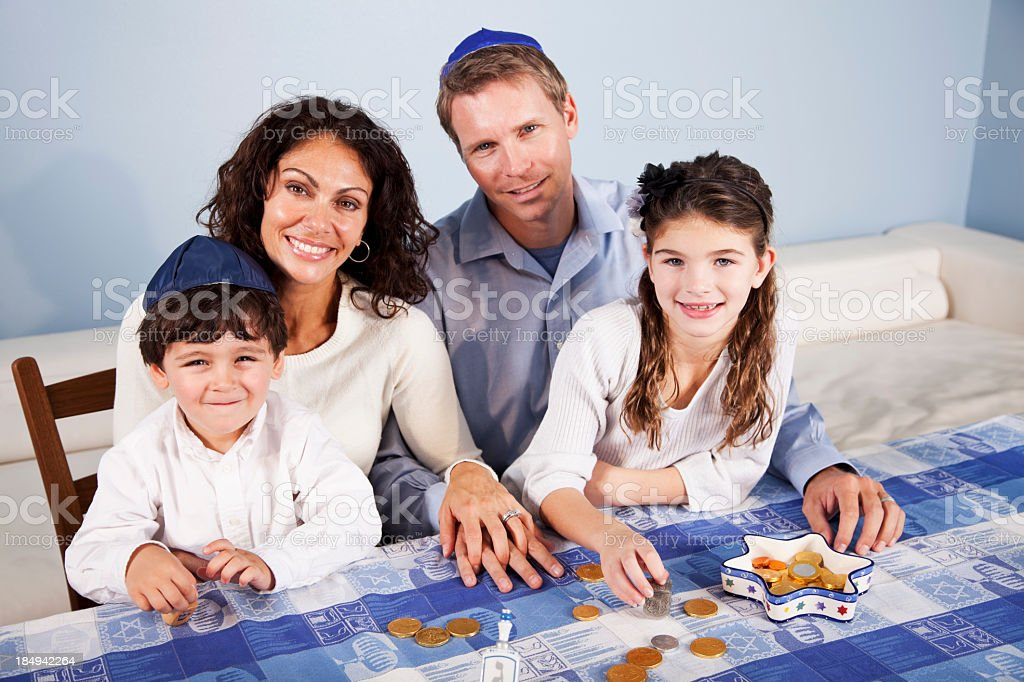 Family at Hanukkah with dreidl and gelt stock photo