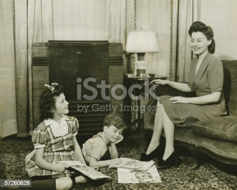 57520540 istock photo Family at home, children (6-7) (10-11) playing on carpet, mother sitting on sofa, (B&W) 57260626