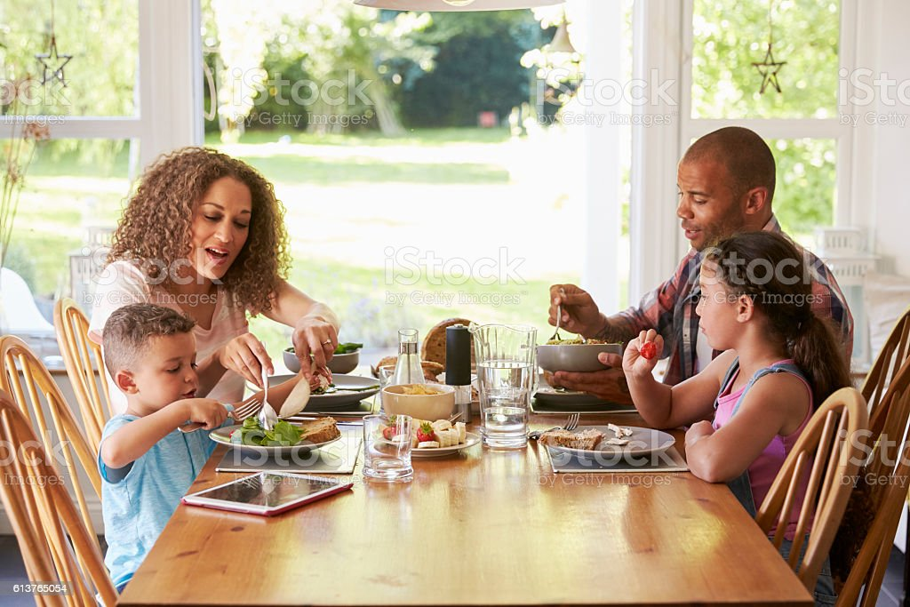 Family At Home Eating Meal In Kitchen Together - foto de stock