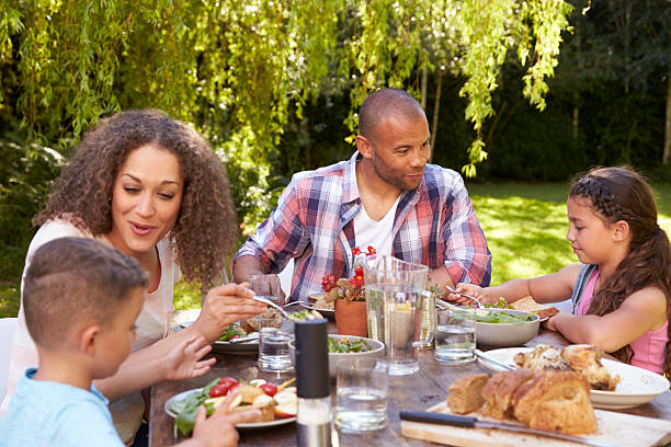 Adult Black Family Enjoying Dinner Together In Their Garden Pictures Images And Stock Photos