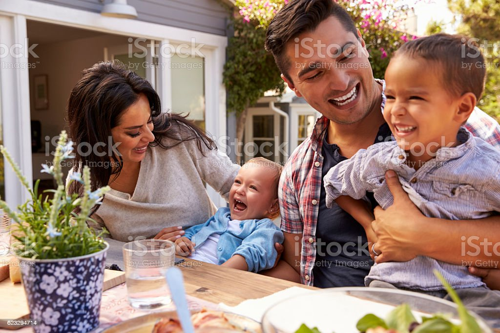Family At Home Eating Outdoor Meal In Garden Together - foto de acervo