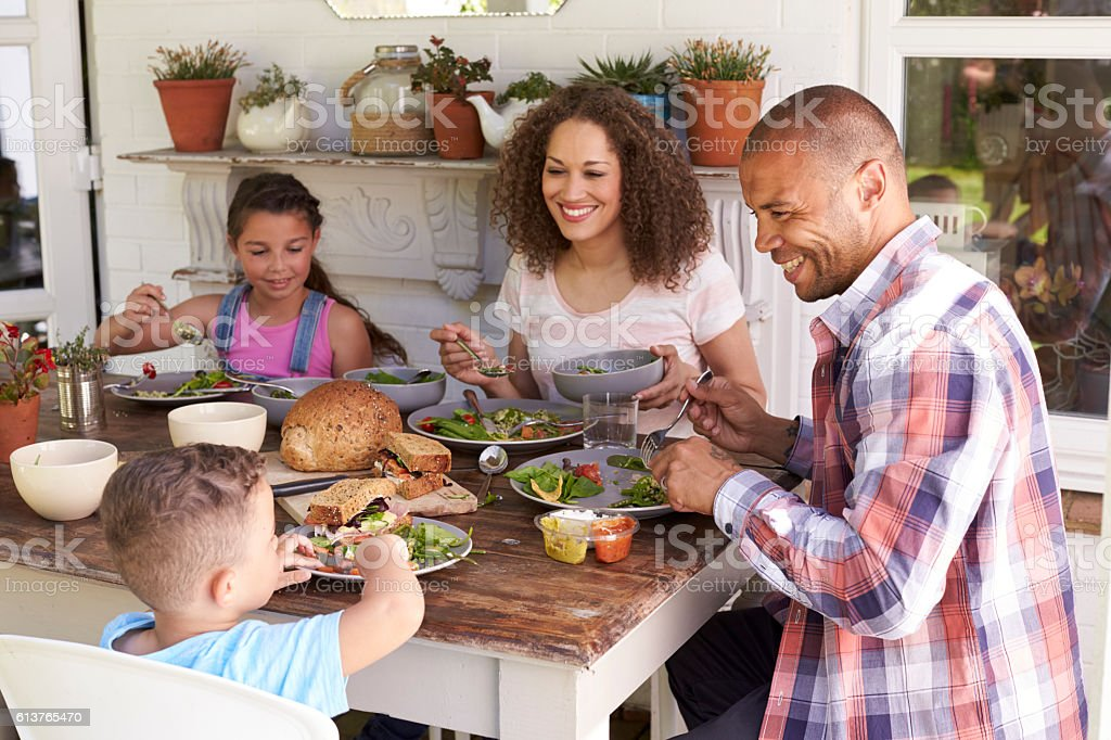 Family At Home Eating Outdoor Meal Together stock photo