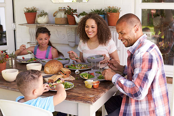 family at home eating outdoor meal together - family dinner stock photos and pictures