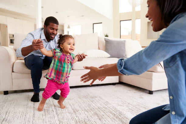 family at home encouraging baby daughter to take first steps - first step stock photos and pictures