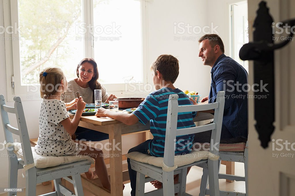 Family At Home In Eating Meal Together - foto de acervo