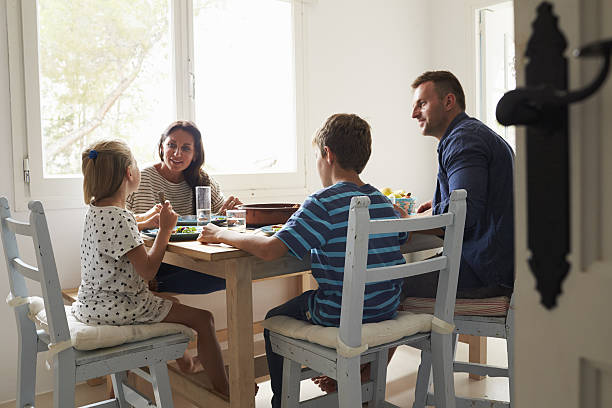 family at home in eating meal together - family dinner stock photos and pictures