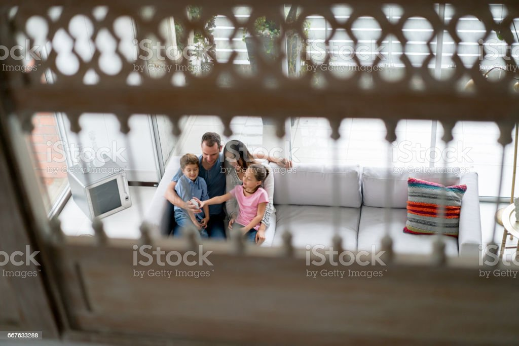 Family at home looking at pictures on a cell phone stock photo