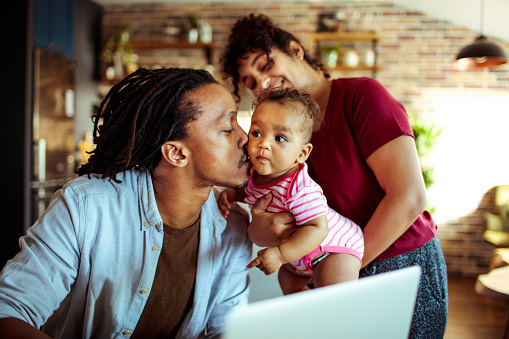 Close up of a young family in their living room using a laptop
