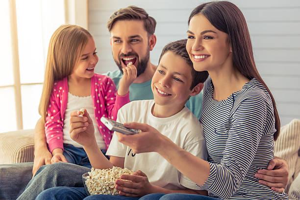 familia en su casa  - family watching tv fotografías e imágenes de stock