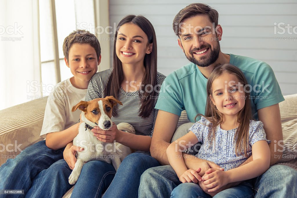 Family at home Beautiful young parents, their cute little daughter and son are looking at camera and smiling, sitting with their cute dog on sofa at home Adult Stock Photo