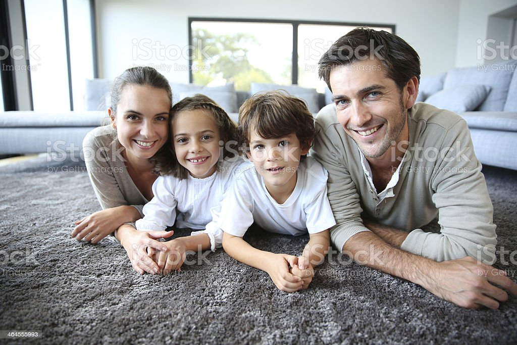 Family at home relaxing on carpet stock photo