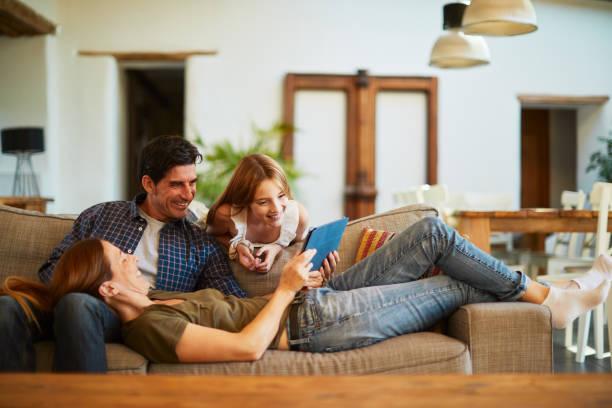 Familie zu Hause teilen ein digitales Tablet und entspannen auf dem Sofa. – Foto
