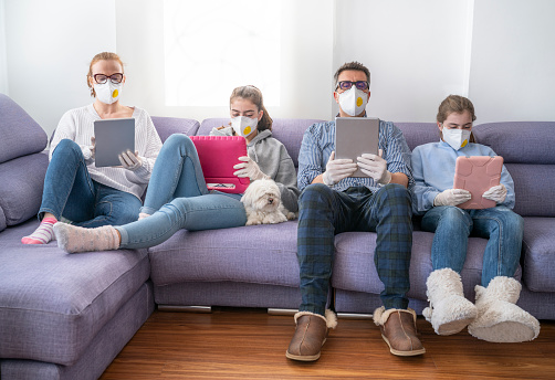 Family at home sofa with mask and tablet pc in quarantine isolation