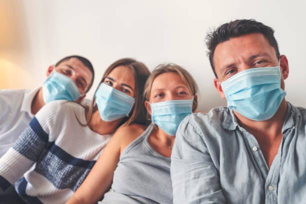 Familie zu Hause mit chirurgischen Masken. Sie sind Brüder und Schwestern. – Foto