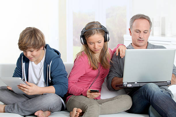 Family at home with technology stock photo