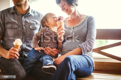 A young adult family sits on a wooden bench inside an ice cream shop, the mother smiling as she feeds her baby daughter a big bite of her waffle ice cream cone.  Horizontal.