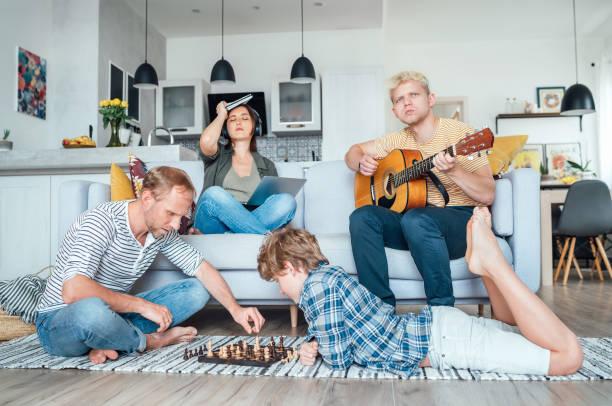 Familie im Wohnzimmer zusammen. Vater spielen Schach mit kleinem Sohn, Mutter lernen Online-Kurs auf Laptop, älteren Sohn spielen akustische Gitarre und Singen von Liedern. Quarantänezeit und Familienkonzept. – Foto