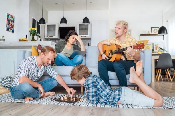 Familia en la sala de estar juntos. Padre jugando ajedrez con el hijo pequeño, madre aprendiendo en línea usando el ordenador portátil, hijo mayor tocando la guitarra acústica y cantando unacando unacando canciones. Tiempo de cuarentena y concepto fami - foto de stock