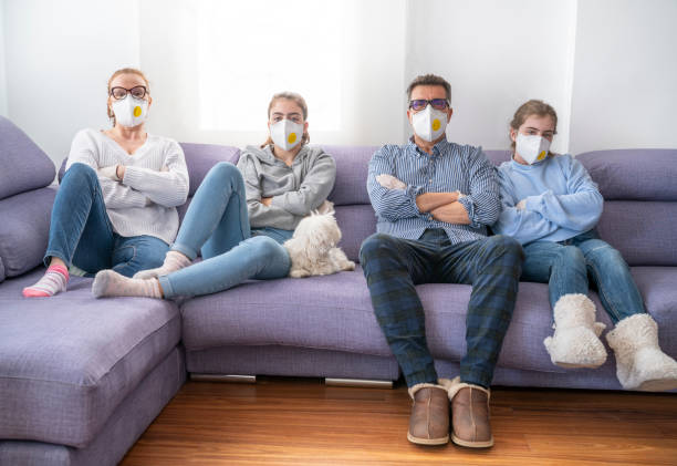 Family at sofe with mask in quarantine isolation against virus Family at home sofa with mask in quarantine isolation against virus COVID-19 Coronavirus Corona Virus confined space stock pictures, royalty-free photos & images