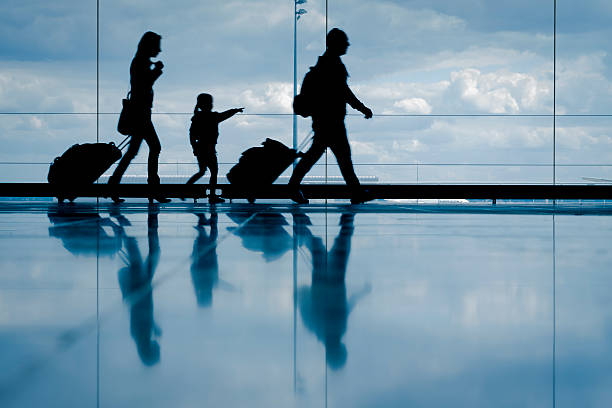 Family at the airport Sihouette of young family with luggage walking at airport, girl pointing at the window val d'oise stock pictures, royalty-free photos & images