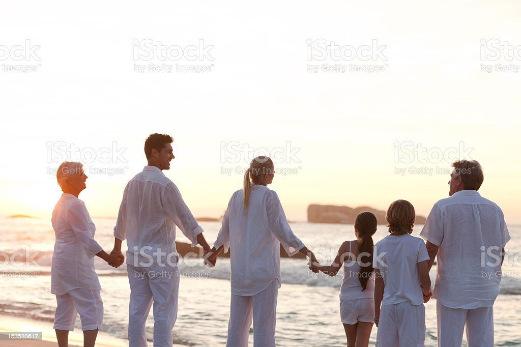 Family at the beach during a sunset royalty-free stock photo