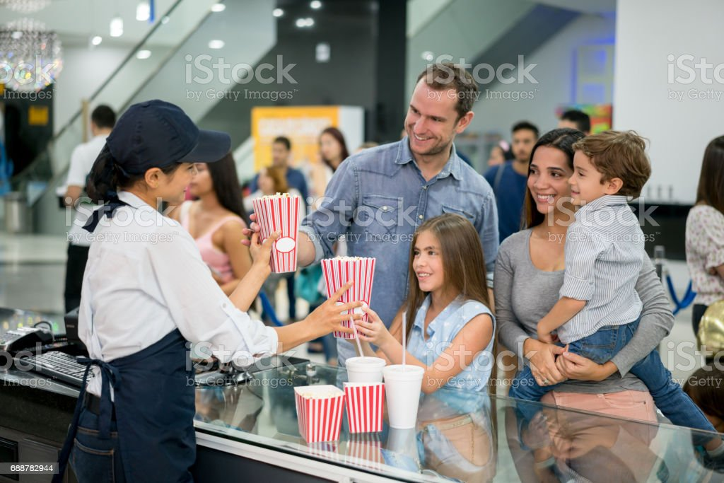Family at the cinema buying food at the candy shop stock photo