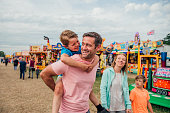 Family enjoying time at the fairground. Dad is carrying his son on his back