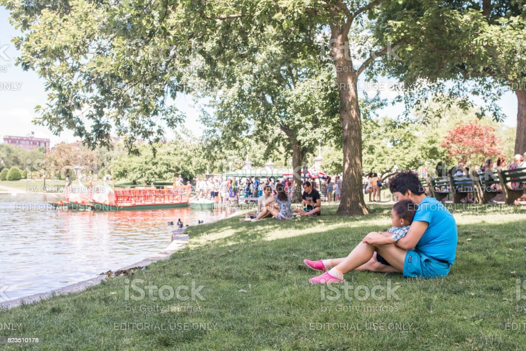 Family at the Frog Pond in Boston Commons in summer stock photo