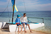 family of two, father and son, enjoying sailing together at hobie cat catamaran, active healthy lifestyle concept