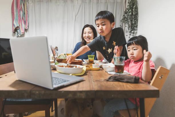 Família participando de video reunião online e jantando juntos em casa - foto de acervo