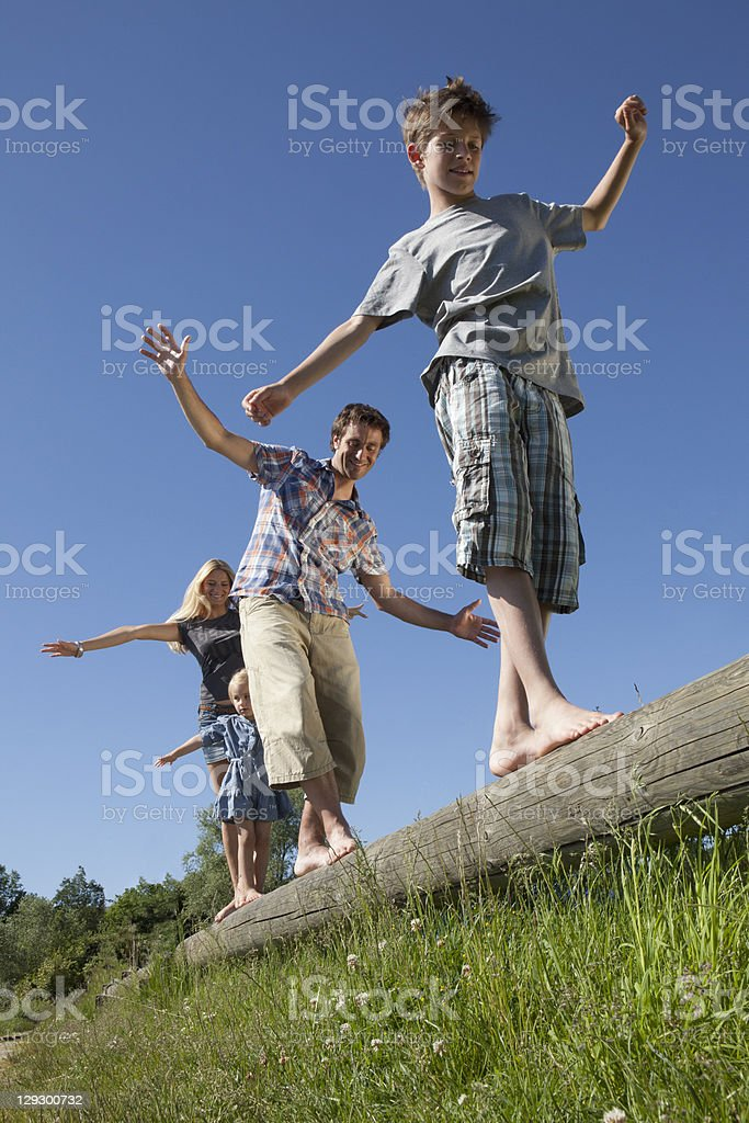 Family balancing on log outdoors stock photo