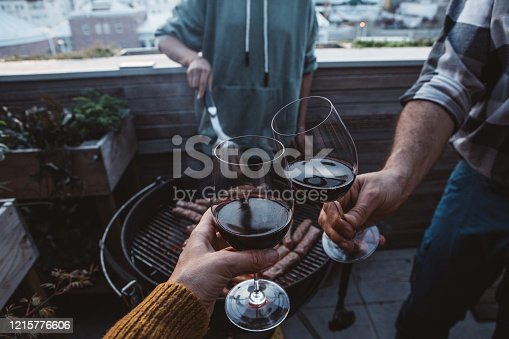 Family on terrace have barbecue during isolation period.They have great time, enjoy in sunset and toasting with wine