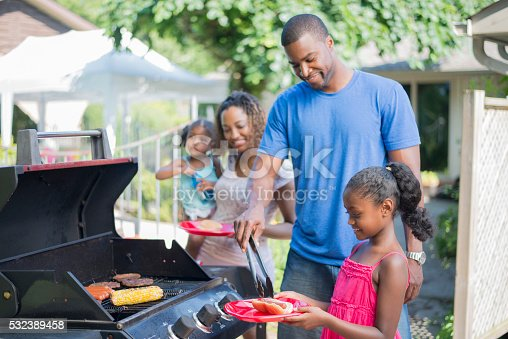 A family of four are outside on a beautiful sunny summer day. They father is barbecuing hot dogs and hamburgers over the grill.
