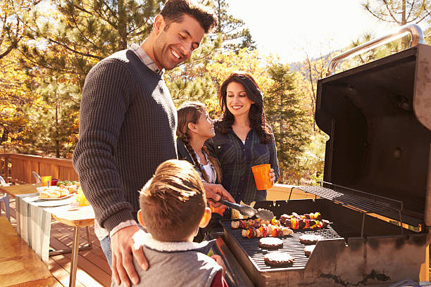 family barbecuing on a deck in the forest - grilled stock photos and pictures