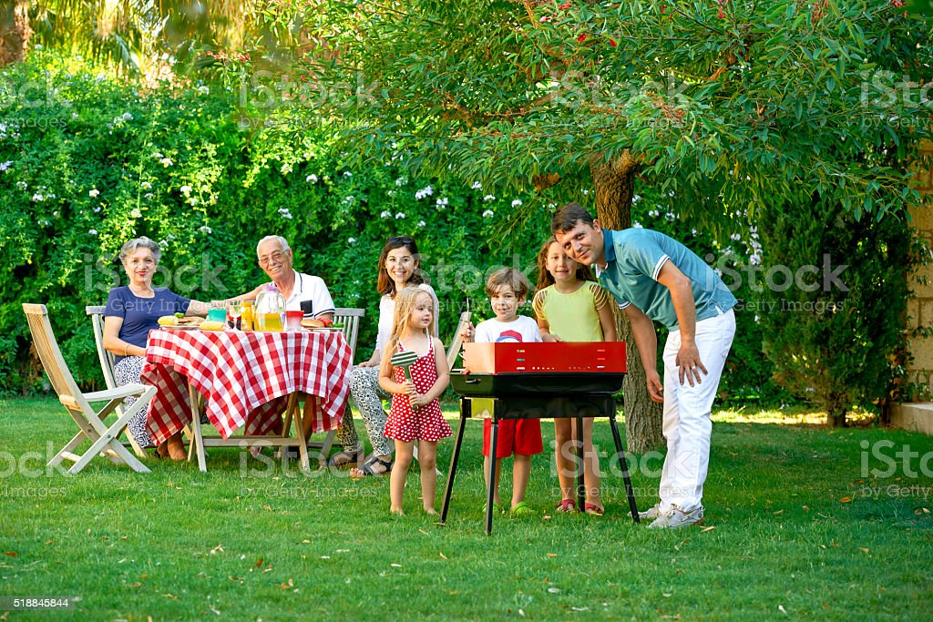 Family barbeques in their backyard. stock photo