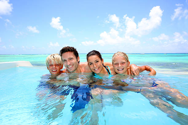 Family bathing in swimming pool stock photo